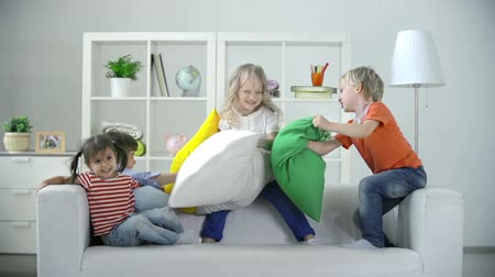 nepořádek : Four kids playing on sofa pillow fighting