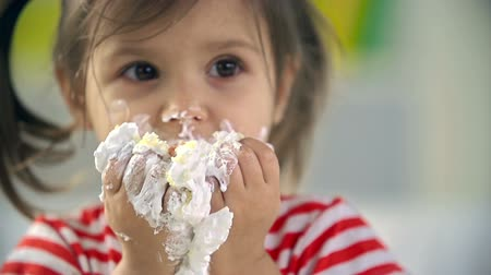 nepořádek : Close up of adorable little girl devouring cake with her hands