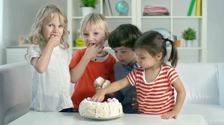 nepořádek : Four kids eating birthday cake with their hands