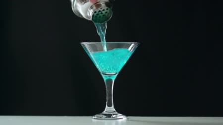 martini glasses : Close up of unrecognizable cropped bartender pouring blue cocktail from shaker to cocktail glass Stock Footage