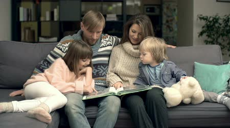 фото : Family of four cuddling on sofa in living room and watching photo book