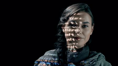 кража : Woman with binary code projected on her face turning to camera and grinning Стоковые видеозаписи