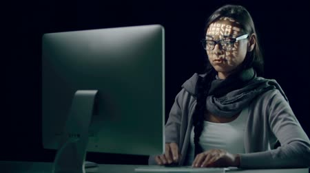 ikili : Woman computing in the dark with binary code projections on her face