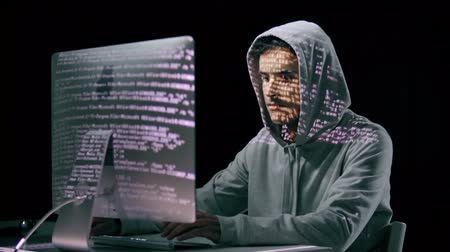 кража : Hacker in hoodie computing with projections on his face Стоковые видеозаписи