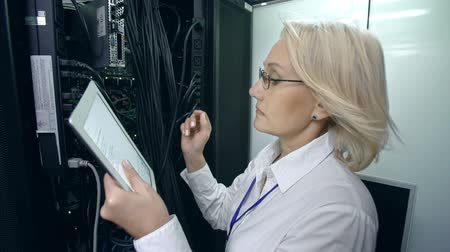 merkez : Tilt up of woman in supercomputer center copying data from rigid drive to her digital tablet device