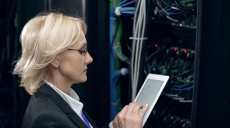 tényező : Female scientific worker checking supercomputer indices and turning to look at camera
