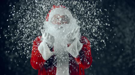 Санта шляпе : Man in Santa Claus costume catching snowflakes in hands and blowing them at camera