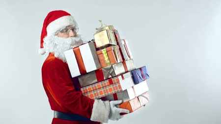 Санта шляпе : Santa Claus passing by camera with stack of gift boxes and giving a wink cheerfully