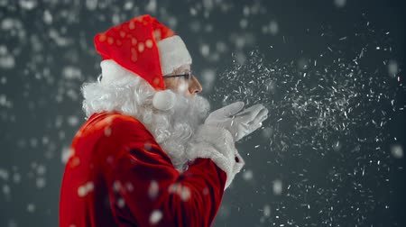 Санта шляпе : Side view of aged man in Santa Claus costume blowing confetti from palms causing snowstorm and turning to camera waving cheerfully Стоковые видеозаписи