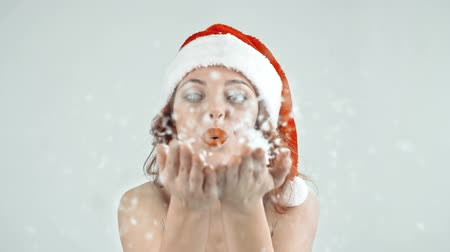 üfleme : Waist up shot of girl in Santa outfit blowing snow flakes in air kiss Stok Video