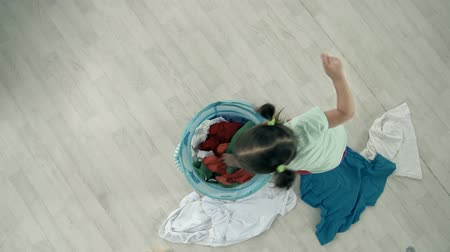 trik : Direct from above shot of little girl throwing out the clothes from buck-basket