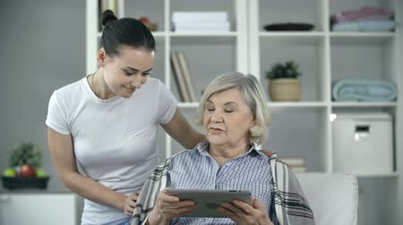комфорт : Elderly patient asking young nurse to help with modern technology