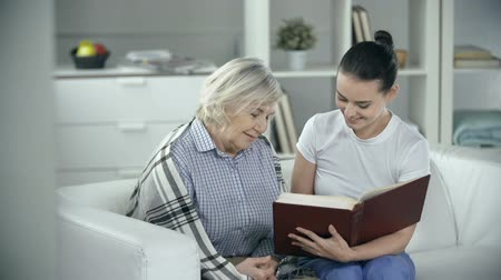 caregiver : Senior patient reading a book with medical worker