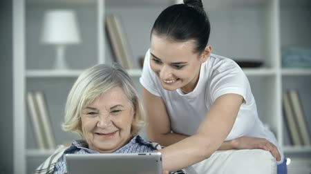 opieka : Nurse and patient laughing together at something on the screen of digital tablet Wideo