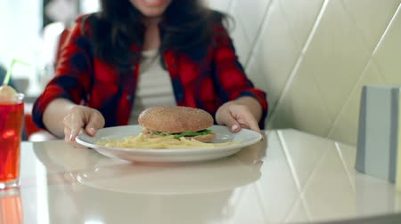 hambúrguer : Cropped unrecognizable woman starting to eat hamburger