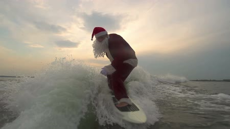santa : Sportive Santa Claus balancing on waves surfboarding at sunset