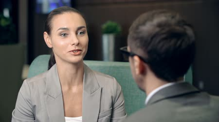 discussion meeting : Smart woman talking to her male business partner sitting with his back to camera Stock Footage