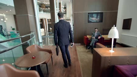 отель : Camera following businessman strolling along the hotel lobby and stopping to answer the phone call Стоковые видеозаписи