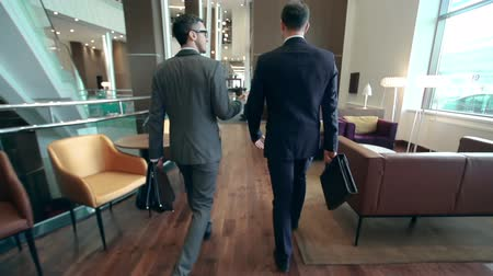 entrance : Camera following two businessmen walking along hotel lobby and discussing issues