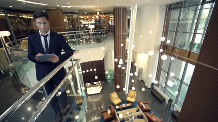 отель : Panoramic fish eye shot of hotel lobby interior with smart businessman standing at staircase and using digital tablet device Стоковые видеозаписи