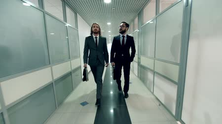 workmate : Two handsome businessmen going along office building corridor and talking