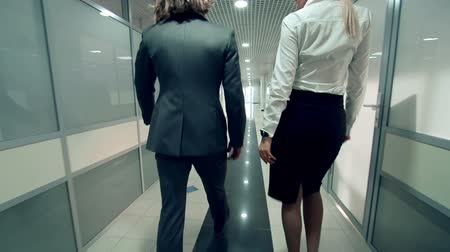 workmate : Camera following man and woman in formalwear going along office hall and talking in slow motion