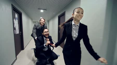 çekme : Three joyous businessmen approaching camera pushing and pulling chair with colleague along the corridor