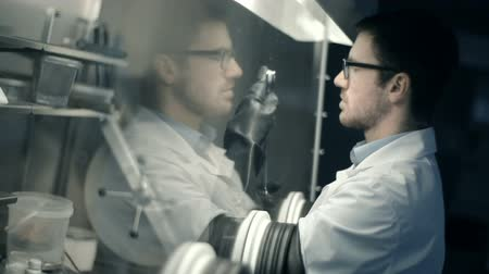 maska : Laboratory technician using isolation glove box chamber in the dark room Wideo