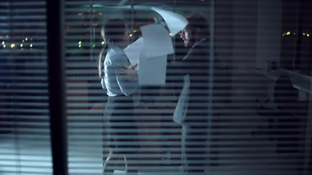 boss : Camera peeping through the cubicle window for colleagues arguing in the darkness