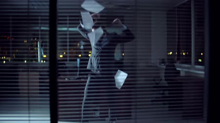 amalucado : Man tossing documents and dancing in the dark empty office