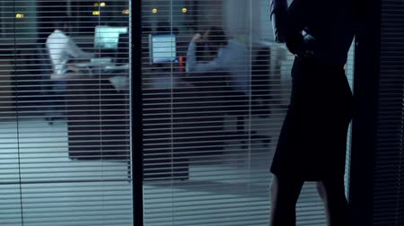 intrigue : Tilt up of business-like woman standing in the dark and watching her male colleagues working