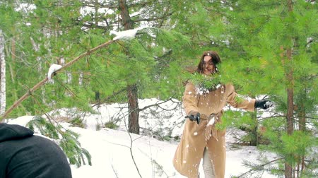 kavga : Carefree couple enjoying their snowball fight in the woods Stok Video