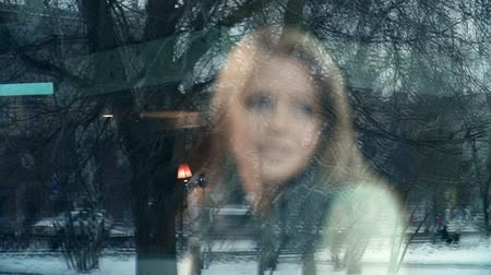 mensagem : Through the window shot of pretty girl disappointed by the news from smartphone message, focus shifting to window cars reflection