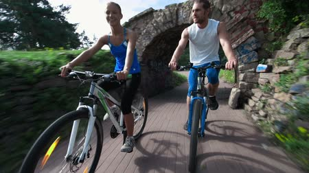 благополучия : Couple of young cyclists riding along the park and having fun