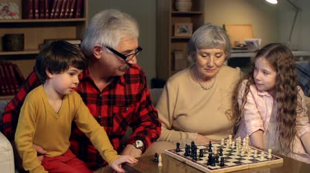 quatro : Grandparents teaching children to play game of chess Vídeos