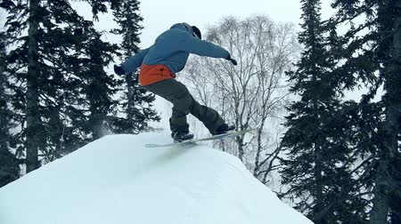 snowboard : Freerider reaching mountain peak and turning snowboard back down in slow motion Stok Video