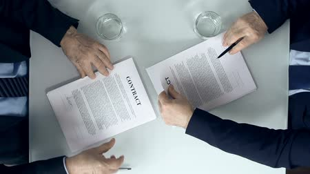 szerződés : Direct from above view of two business parties signing respective copy of a contract and congratulating each other with firm handshake