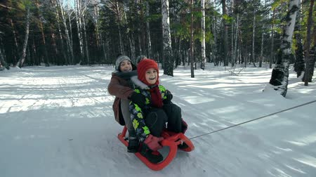 günler : Slow motion of man approaching camera pulling his two kids in sled