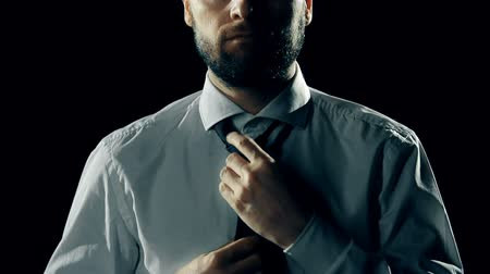 düşünceli : Mid-section of man putting his tie on in the dark Stok Video