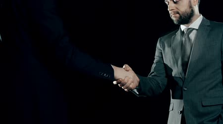 назначение : Tilt down the two businessmen shaking hands in the darkness