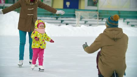 patim : Joyous family at the skating rink, sweet baby learning to skate, walking on ice from mother to father Vídeos