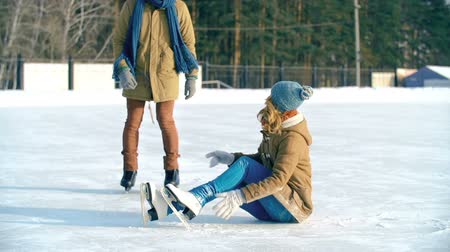 баланс : Pretty girl sitting on ice in skates dusting her clothes down from snow, guy helping her up