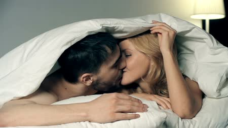 amantes : Playful couple kissing under duvet