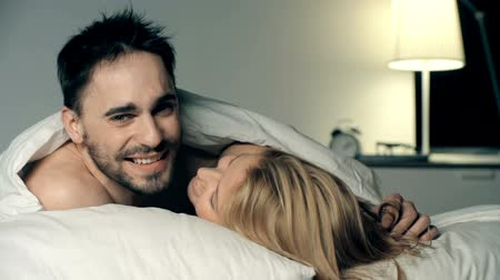 amantes : Close up of man lying in bed and looking straight at camera while his girlfriend is kissing him