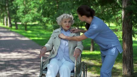 caregiver : Static camera shot of female nurse talking politely to her patient in wheelchair outdoors