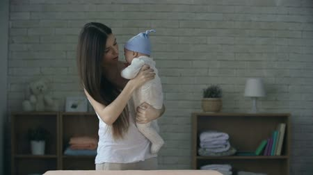 kisbaba : Close up of mother standing in the middle of the room trying to soothe her crying baby