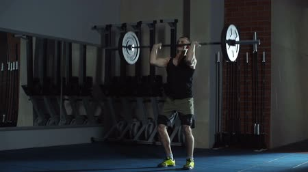 vzpírání : Close up of athletic man performing overhead squats in empty dark gym