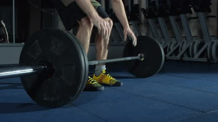 sportsmen : Low section of unrecognizable sportsman gripping barbell with powdered hands