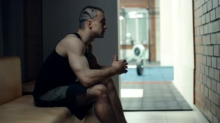 vzpírání : Side view of athletic man with pattern trimming leaving the room for gym