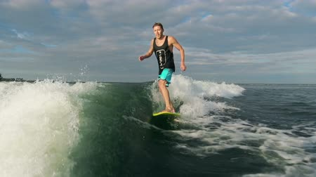 surf : Tracking shot of wake surfer catching waves in slow motion